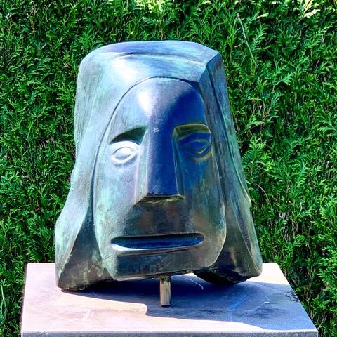 bronzen beeld portret van man groene achtergrond